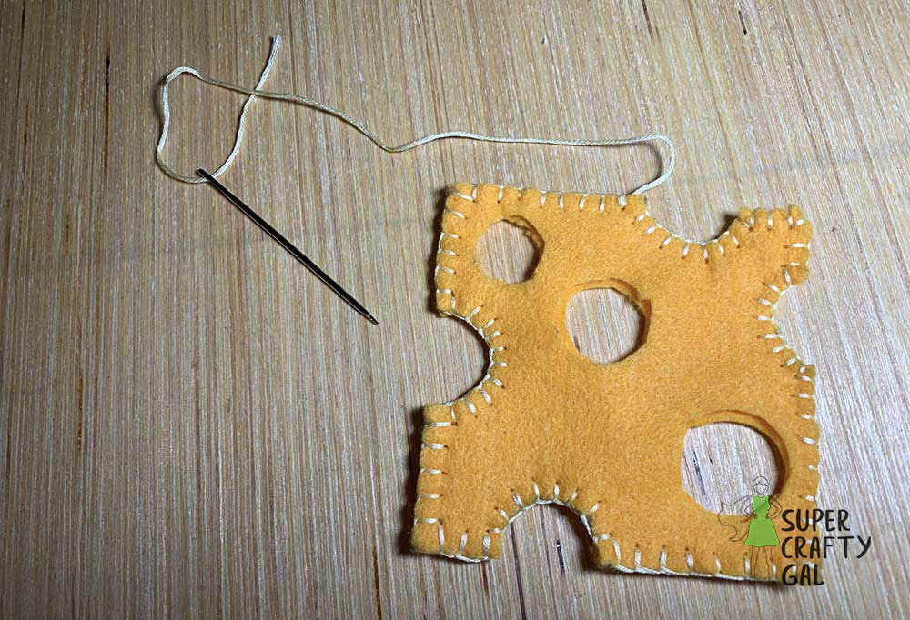 felt cheese being sewn with embroidery thread and needle.