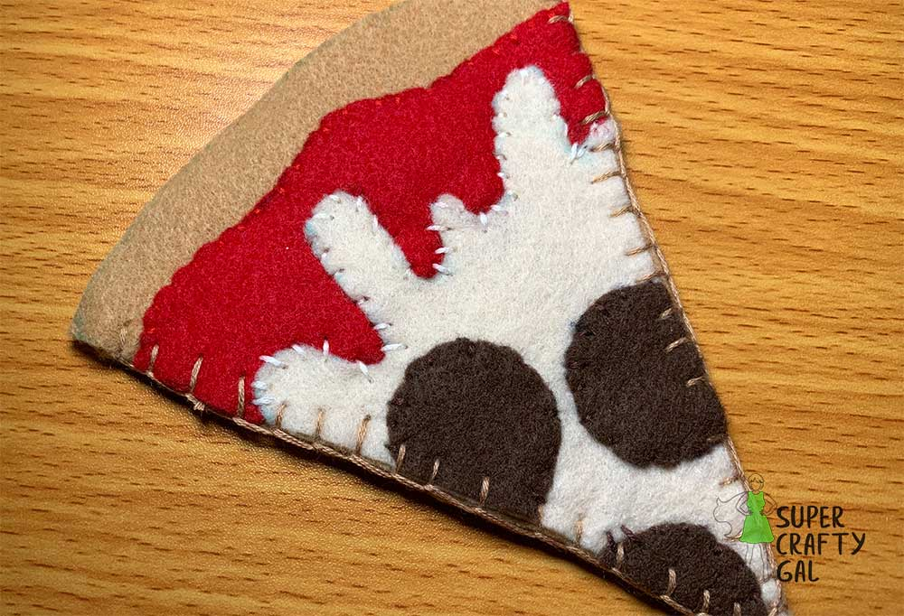 sides of felt pizza sewn together using a blanket stitche