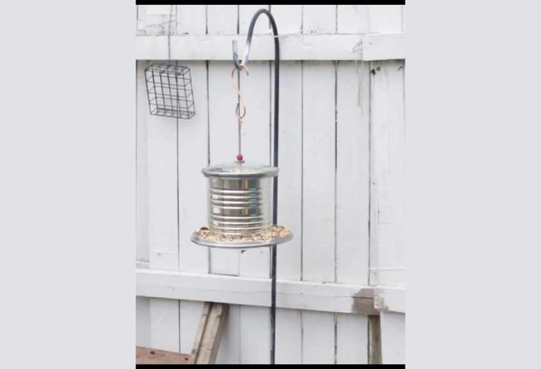 Bird feeder made from glass pot lids, a large metal can and heavy grade wire