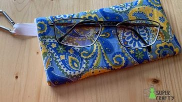 Eyeglass case made from yellow and blue paisley fabric with pair of glasses sitting on top