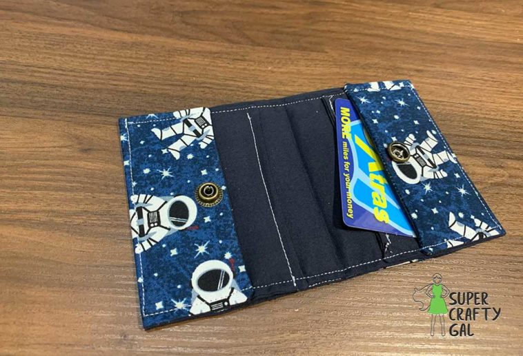 Wallet laying open with loyalty card laying open on wood table