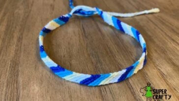 Dark Blue, Teal, Light Yellow, and White embroidery floss anklet on a wooden surface
